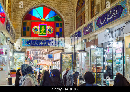 TEHRAN, IRAN - MAY 22, 2017: Crowd of people in row of Grand Bazaar with stalls of dishes - Stock Photo