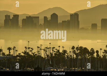 Calm sunrise, masked by fog layer, over the San Diego skyline, with North San Diego Bay and docked sailboats off Shelter Island, California, USA - Stock Photo