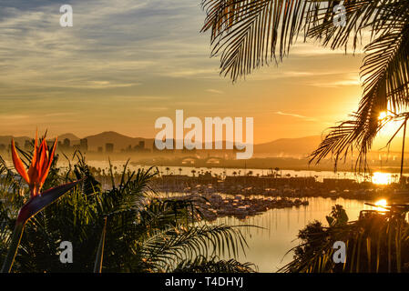 Calm bright sunrise over the San Diego skyline, with North San Diego Bay and docked sailboats off Shelter Island, California, USA - Stock Photo