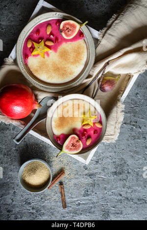 Semolina pudding with homemade pomegranate syrup, decorated with star fruit, figs and almonds - Stock Photo