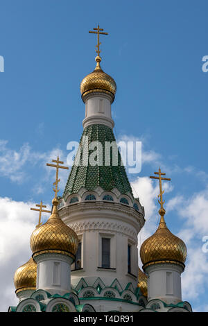 The golden gilded domes of the Russian Church of St Nicholas the Miracle-Maker in Sofia Bulgaria against blue sky. - Stock Photo