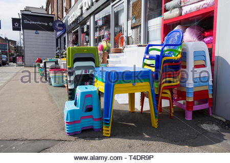Multicoloured plastic items outside an ironmongers store in London, UK - Stock Photo
