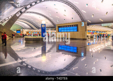 Doha, Qatar - February 24, 2019: Qatar Airways check in passengers in the new and modern Hamad International Airport or Doha Hamad Airport, reflected
