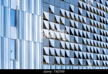 Elements of modern city architecture decorative abstract metal suspended facing of the external walls of a sunlit multistory building, made in the for - Stock Photo