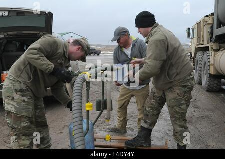 U.S. Army Sgt. David Fuegen, right, and Spc. Tracy Lennick, members with Company A, 139th Brigade Support Battalion, South Dakota Army National Guard, provide drinkable water to Lester Iron Cloud at Sharps Corner, S.D, on the Pine Ridge Reservation, March 25, 2019. Thirteen SDARNG Soldiers were activated for state duty in Pine Ridge after a county waterline failed due to extreme flooding leaving residents in seven communities without water in their homes. - Stock Photo