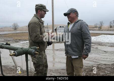 Lester Iron Cloud thanks U.S. Army Spc. Tracy Lennick, with Company A, 139th Brigade Support Battalion, South Dakota Army National Guard, after receiving drinkable water at Sharps Corner, S.D, on the Pine Ridge Reservation, March 25, 2019. Thirteen SDARNG Soldiers were activated for state duty in Pine Ridge after a county waterline failed due to extreme flooding leaving residents in seven communities without water in their homes. - Stock Photo