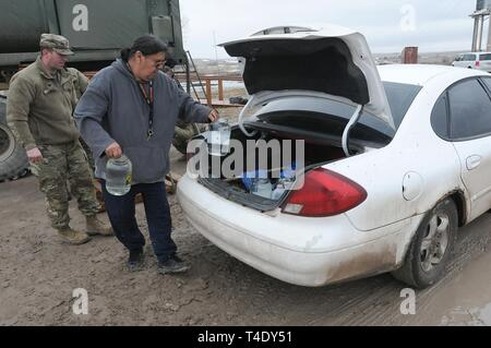 Lester Rowland loads containers of drinkable water into his car with the help of U.S. Army Spc. Tracy Lennick, Company A, 139th Brigade Support Battalion, South Dakota Army National Guard, at Sharps Corner on the Pine Ridge Reservation, March 25, 2019. Thirteen SDARNG Soldiers were activated for state duty in Pine Ridge after a county waterline failed due to extreme flooding leaving residents in seven communities without water in their homes. - Stock Photo