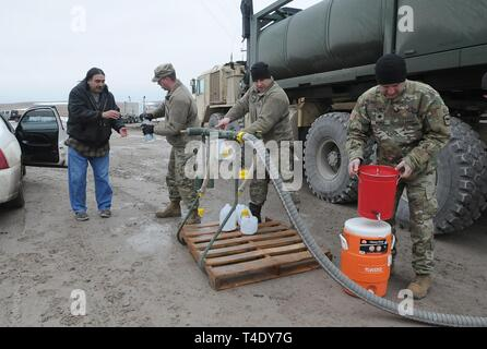 From left) South Dakota Army National Guard Soldiers Spc. Tracy Lennick, Sgt. David Fuegen and Lt. Col. Lew Weber fill containers with drinkable water for residents of Sharps Corner on the Pine Ridge Reservation, S.D., March 25, 2019. Thirteen SDARNG Soldiers with Company A, 139th Brigade Support Battalion, were activated for state duty in Pine Ridge after a county waterline failed due to extreme flooding leaving residents in seven communities without water in their homes. - Stock Photo