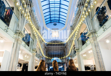 Athens, Greece - 26 Mar 2016: Low anlge view of majestic illumination inside the passage of H and M fashion store on Ermou 54 street with multiple led lights inside the old vintage building - Stock Photo