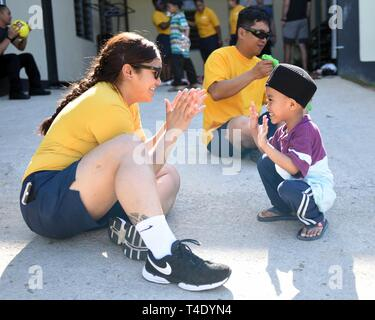 LANGKAWI, Malaysia (March 28, 2019) - Hospital Corpsman 2nd Class Denise Atualevao, from San Diego, attached to U.S. 7th Fleet Flagship USS Blue Ridge (LCC 19), plays patty cake with a child at Rumah Nur Kasih Langkawi Orphanage during a community relations event. Blue Ridge is the oldest operational ship in the Navy and, as 7th Fleet command ship, actively works to foster relationships with allies and partners in the Indo-Pacific Region. - Stock Photo