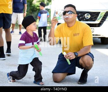LANGKAWI, Malaysia (March 28, 2019) - Master-at-Arms 2nd Class Michael Flores, from Santa Paula, Calif., attached to U.S. 7th Fleet Flagship USS Blue Ridge (LCC 19), blows bubbles with a child at Rumah Nur Kasih Langkawi Orphanage during a community relations event. Blue Ridge is the oldest operational ship in the Navy and, as 7th Fleet command ship, actively works to foster relationships with allies and partners in the Indo-Pacific Region. - Stock Photo