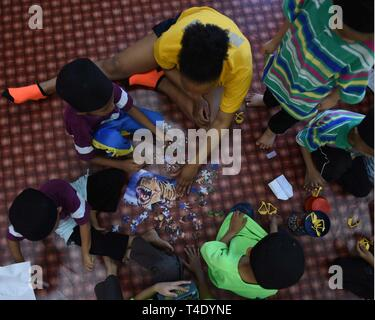 LANGKAWI, Malaysia (March 28, 2019) - Logistics Specialist 2nd Class Egypt Scott, from Buffalo, N.Y., attached to U.S. 7th Fleet Flagship USS Blue Ridge (LCC 19), helps children assembles a puzzle at Rumah Nur Kasih Langkawi Orphanage during a community relations event. Blue Ridge is the oldest operational ship in the Navy and, as 7th Fleet command ship, actively works to foster relationships with allies and partners in the Indo-Pacific Region. - Stock Photo