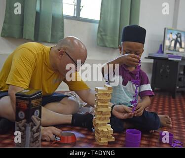 LANGKAWI, Malaysia (March 28, 2019) - Intelligence Specialist 1st Class John Alumia, from Temecula, Calif., attached to U.S. 7th Fleet Flagship USS Blue Ridge (LCC 19), plays monkeys in a barrel with a child at Rumah Nur Kasih Langkawi Orphanage during a community relations event. Blue Ridge is the oldest operational ship in the Navy and, as 7th Fleet command ship, actively works to foster relationships with allies and partners in the Indo-Pacific Region. - Stock Photo