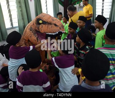 LANGKAWI, Malaysia (March 28, 2019) - Chief Information Systems Technician Steve Hoover, from Lompoc, Calif., attached to U.S. 7th Fleet Flagship USS Blue Ridge (LCC 19), wears a dinosaur costume while playing with a child at Rumah Nur Kasih Langkawi Orphanage during a community relations event. Blue Ridge is the oldest operational ship in the Navy and, as 7th Fleet command ship, actively works to foster relationships with allies and partners in the Indo-Pacific Region. - Stock Photo