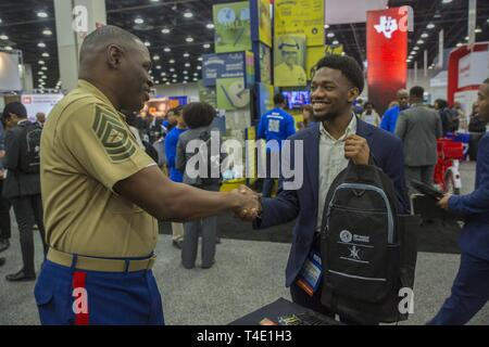 Marine Master Sgt. Damian Cason, a career recruiter with the Marine Corps Recruiting Command, shakes hands with Ansumana Bangura, a junior at Cornell University, during a National Society of Black Engineers conference career fair in Detroit, Michigan, March 28. NSBE is holding its 45th annual national convention consisting of various programs and workshops that are designed to benefit grade school, collegiate, technical, professional and international attendees and the U.S. Marine Corps is a partner organization. Marines partner with organizations like NSBE to ensure its message of opportunity - Stock Photo