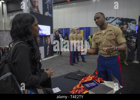 Marines Staff Sgt. Christopher Patterson, A recruiter from Recruiting Station Albuquerque, speaks with Zaniyah Sealey, a sophomore from the University of Georgia, during a National Society of Black Engineers conference career fair in Detroit, Michigan, March 28, 2019. NSBE is holding its 45th annual national convention consisting of various programs and workshops that are designed to benefit grade school, collegiate, technical, professional and international attendees and the U.S. Marine Corps is a partner organization. Marines partner with organizations like NSBE to ensure its message of oppo - Stock Photo