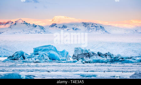 Icebergs float on Jokulsarlon glacier lagoon at sunrise, with background mountain peaks lit by sunrise, in Iceland. - Stock Photo