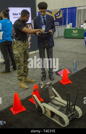 Marine Sgt. Jeremy McBroom, explosive ordnance disposal technician with 2nd EOD Company, 8th Engineer Support Battalion, assists Avi Martin, a freshman at San Diego State University, operate the EOD robot Sug-V during a National Society of Black Engineers conference career fair in Detroit, Michigan, March 29, 2019. NSBE is holding its 45th annual national convention consisting of various programs and workshops that are designed to benefit grade school, collegiate, technical, professional and international attendees and the U.S. Marine Corps is a partner organization. Marines partner with organ - Stock Photo