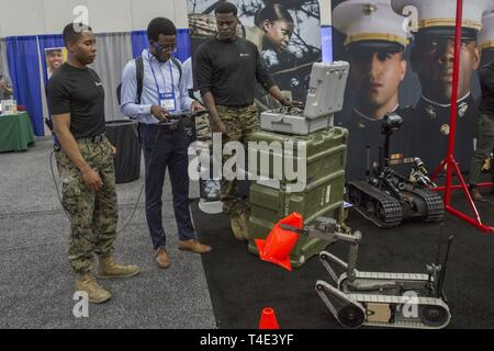 Marines Sgt. Jeremy McBroom and Staff Sgt. Steven Bellamy, explosive ordnance disposal technicians for 2nd EOD Company, 8th Engineer Support Battalion, discuss EOD robots with Chigozie Erondu, a freshman at George Mason University, during a National Society of Black Engineers conference career fair in Detroit, Michigan, March 29, 2019. NSBE is holding its 45th annual national convention consisting of various programs and workshops that are designed to benefit grade school, collegiate, technical, professional and international attendees and the U.S. Marine Corps is a partner organization. Marin - Stock Photo