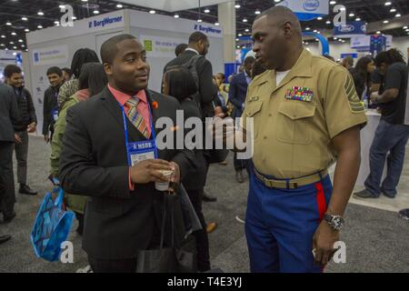 Jafari Williams, a junior at Morgan State University, talks about career opportunities with Master Sgt. Damian Cason, a career recruiter with the Marine Corps Recruiting Command, during a National Society of Black Engineers conference career fair in Detroit, Michigan, March 29, 2019. NSBE is holding its 45th annual national convention consisting of various programs and workshops that are designed to benefit grade school, collegiate, technical, professional and international attendees and the U.S. Marine Corps is a partner organization. Marines partner with organizations like NSBE to ensure its - Stock Photo