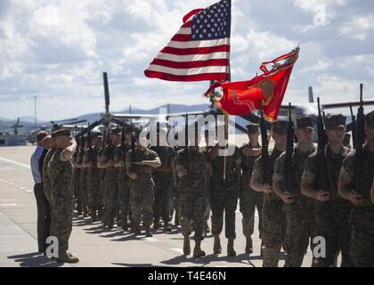 Leaders with Marine Medium Tiltrotor Squadron 166, Marine Aircraft Group 16, 3rd Marine Aircraft Wing, salute the American flag during a change of command ceremony at Marine Corps Air Station Miramar, Calif., March 28, 2019. The passing of the colors from Lt. Col. Charles E. Bodwell to Lt. Col. James C. Ford III signifies the transfer of responsibility, authority and accountability from the outgoing commanding officer to the incoming commanding officer. - Stock Photo