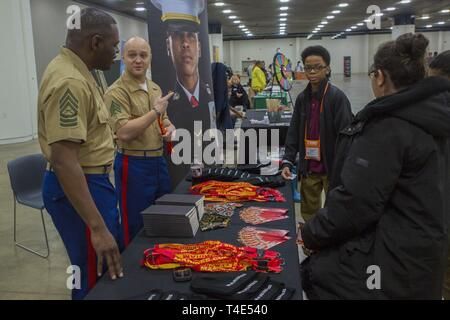 Marine Master Sgt. Damian Cason, a career recruiter with the Marine Corps Recruiting Command, and Sgt. Jacob Droste, a recruiter at Recruiting Substation Wyandotte, talk about the Marine Corps with Nathanael Stewart, a seventh grade student at Betty Shabazz Academy, during a National Society of Black Engineers conference STEAMFest in Detroit, March 30, 2019. NSBE is holding its 45th annual national convention consisting of various programs and workshops that are designed to benefit grade school, collegiate, technical, professional and international attendees and the U.S. Marine Corps is a part - Stock Photo