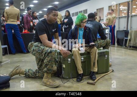 Marine Sgt. Jeremy McBroom, explosive ordnance disposal technician with 2nd EOD Company, 8th Engineer Support Battalion, assists Manny Valle, an eighth grade student at Next Generation Leadership Academy, operate an EOD robot during a National Society of Black Engineers conference STEAMFest in Detroit, March 30, 2019. NSBE is holding its 45th annual national convention consisting of various programs and workshops that are designed to benefit grade school, collegiate, technical, professional and international attendees and the U.S. Marine Corps is a partner organization. Marines partner with or - Stock Photo
