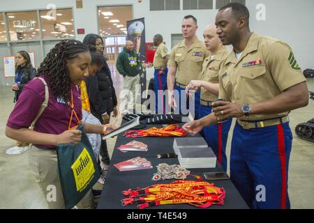Marquita Hopkins, a sixth grade student at Kershaw Elementary, receives a Marines notepad from Staff Sgt. Christopher Patterson, a recruiter from Recruiting Station Albuquerque, during a National Society of Black Engineers conference STEAMFest in Detroit, March 30, 2019. NSBE is holding its 45th annual national convention consisting of various programs and workshops that are designed to benefit grade school, collegiate, technical, professional and international attendees and the U.S. Marine Corps is a partner organization. Marines partner with organizations like NSBE to ensure its message of o - Stock Photo