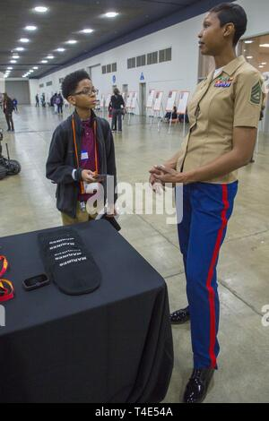 Nathanael Stewart, a seventh grade student at Betty Shabazz Academy, discusses Marine traditions with Gunnery Sgt. Latyra Sayers, a career recruiter with Recruiting Station San Diego, during a National Society of Black Engineers conference STEAMFest in Detroit, March 30, 2019. NSBE is holding its 45th annual national convention consisting of various programs and workshops that are designed to benefit grade school, collegiate, technical, professional and international attendees and the U.S. Marine Corps is a partner organization. Marines partner with organizations like NSBE to ensure its messag - Stock Photo