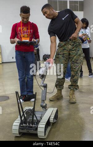 Will Roberson, a junior at Shady Side Academy, controls an Explosive Ordnance Disposal robot with Sgt. Jeremy McBroom, explosive ordnance disposal technician with 2nd EOD Company, 8th Engineer Support Battalion, during a National Society of Black Engineers conference STEAMFest in Detroit, March 30, 2019. NSBE is holding its 45th annual national convention consisting of various programs and workshops that are designed to benefit grade school, collegiate, technical, professional and international attendees and the U.S. Marine Corps is a partner organization. Marines partner with organizations li - Stock Photo
