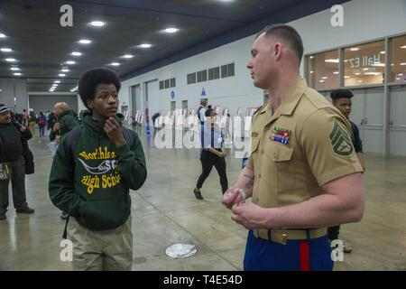 Aaron Holley, a junior at Northland High School, receives information about joining the Marine Corps from Staff Sgt. Jeff Frantjeskos, a career recruiter from Recruiting Substation Wyandotte, during National Society of Black Engineers' conference STEAMFest in Detroit, March 30, 2019. NSBE is holding its 45th annual national convention consisting of various programs and workshops that are designed to benefit grade school, collegiate, technical, professional and international attendees and the U.S. Marine Corps is a partner organization. Marines partner with organizations like NSBE to ensure its - Stock Photo