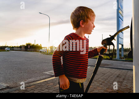 Child holding the hose of a fuel pump at sunset at a gas station. - Stock Photo