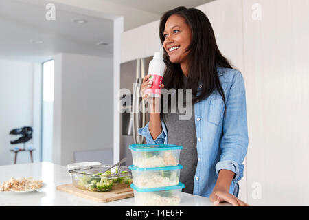 Woman In Kitchen Preparing Healthy Meal Drinking Protein Shake From Bottle - Stock Photo