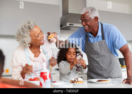 Grandparents In Kitchen With Granddaughter Making Pancakes Together - Stock Photo