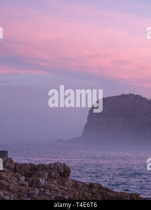 The Heads, Knsyna, Garden Route, South Africa. Rocky outcrop at the top of the lagoon, photographed in mist at sunset.