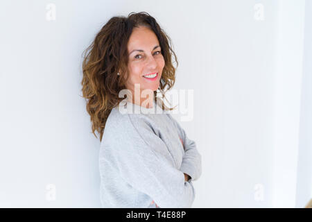 Beautiful middle age woman with curly hair smiling cheerful and happy with arms crossed, laughing with a big smile on face showing teeth over white is - Stock Photo