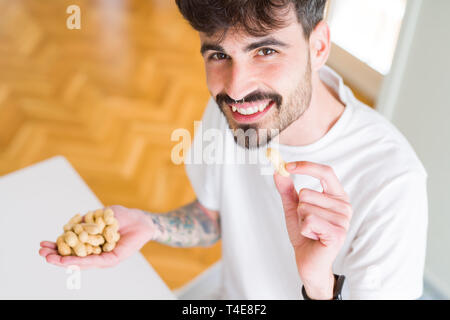 Young man eating peanuts, close up of hand with a bunch of healthy nuts - Stock Photo