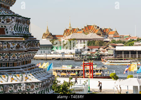 BANGKOK, THAILAND - MARCH 2019: view over the roofs of Wat Pho Reclining Buddha temple complex with Wat Arun stupa on the foreground - Stock Photo