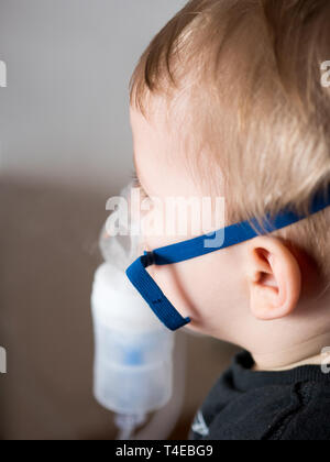 Portrait of small caucasian boy with oxygen mask - Stock Photo