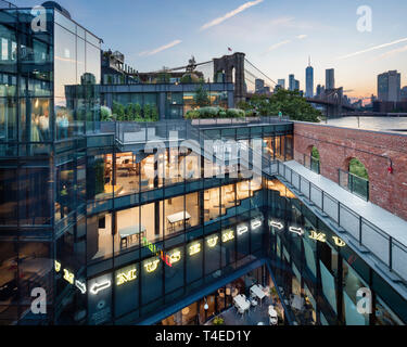 View from the upper level of the public roof deck onto the courtyard and the Manhattan skyline. Empire Stores, Brooklyn, United States. Architect: Stu - Stock Photo