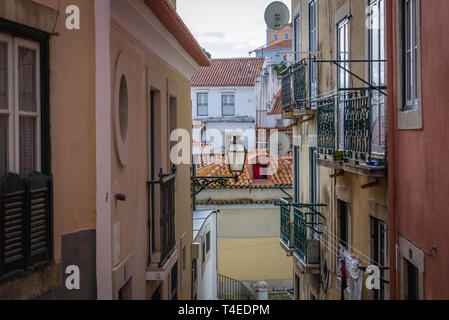 Narrow street in Alfama district of Lisbon, Portugal - Stock Photo