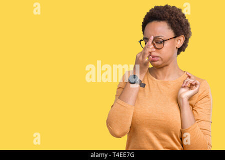 Young beautiful african american woman wearing glasses over isolated background smelling something stinky and disgusting, intolerable smell, holding b - Stock Photo