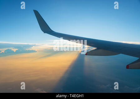 View of airplane wing and sunset sky. Plane in flight, clouds project long shadows. - Stock Photo