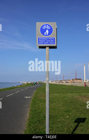 Shared path please consider other path users sign, mounted on galvanized steel post on grass verge at side of cycle path and footpath in Blackpool uk - Stock Photo