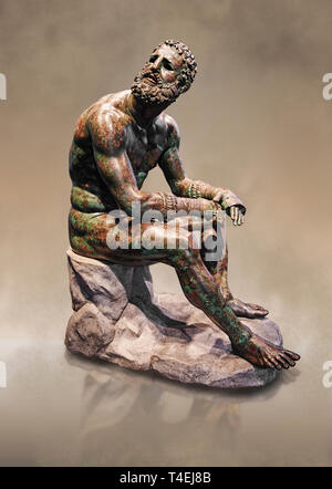 Rare original Greek bronze statue of an Athlete after a boxing match, a 1st cent BC. The athlete, seated on a boulder, is resting after a boxing match - Stock Photo