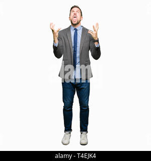 Handsome business man wearing suit and tie crazy and mad shouting and yelling with aggressive expression and arms raised. Frustration concept. - Stock Photo