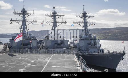 Scotland (March 30, 2019) - The British White Ensign flies aboard the British Royal Navy Albion-class amphibious transport dock HMS Albion (L14) while the Arleigh Burke-class guided-missile destroyers USS Gravely (DDG 107), USS Carney (DDG 64), and USS Porter (DDG 78) are moored at HMNB Clyde in Faslane, Scotland, March 30, 2019. Carney, forward-deployed to Rota, Spain, is on its sixth patrol in the U.S. 6th Fleet area of operations in support of regional allies and partners as well as U.S. national security interests in Europe and Africa. - Stock Photo