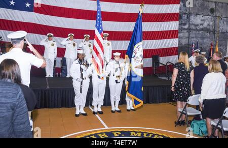 SAN DIEGO (April 3, 2019) Service Members and Civilians in attendance observe the National Anthem during the USS John P. Murtha's (LPD 26) change of command ceremony. USS John P. Murtha is the 10th San Antonio-class amphibious transport dock ship of the United States Navy and is named in honor of Congressman John Murtha of Pennsylvania and homeported in San Diego and is part of Naval Surface Forces and U.S. 3rd Fleet. - Stock Photo