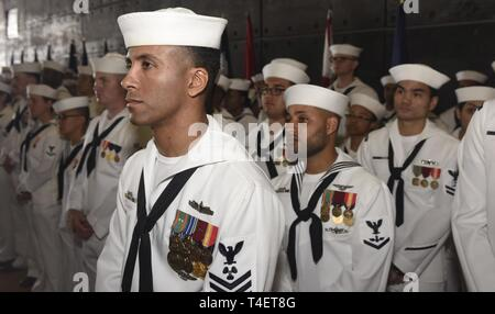 SAN DIEGO (April 3, 2019) Sailors attached to the USS John P. Murtha (LPD 26) observe the ship's change of command ceremony. USS John P. Murtha is the 10th San Antonio-class amphibious transport dock ship of the United States Navy and is named in honor of Congressman John Murtha of Pennsylvania and homeported in San Diego and is part of Naval Surface Forces and U.S. 3rd Fleet. - Stock Photo