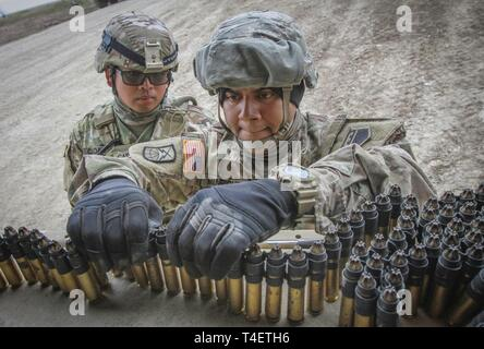 Army Reserve Spc. Ricardo Manriquez (right), a communication specialist and native of Sylmar, California, assigned to the 307th Chemical Company, 453rd Chemical Battalion, 209th Regional Support Group, 76th Operational Response Command links blank .50 caliber ammunition together in the back of a vehicle at Fort Riley, Kansas, April 4, as Spc. James Cadaoas, a chemical, biological, radiological and nuclear (CBRN) specialist and native of Carson, California, also assigned to the 307th Chem. Co, supervises. More than 450 Army Reserve Soldiers from around the country are participating in a three-w - Stock Photo